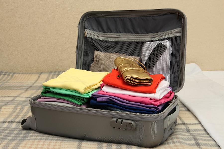 bigstock-Open-grey-suitcase-with-clothi-41253598